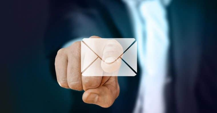 Business man pointing to an email icon on glass